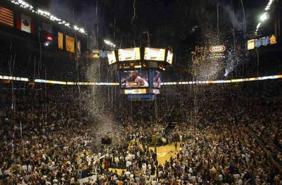 Confetti and streamers fall as fans and players celebrate following game 7 of the NBA Finals at the SBC Center in San Antonio on Thursday, June 23, 2005. The Spurs beat Detroit to win the championship. BILLY CALZADA  / STAFF (SAN ANTONIO EXPRESS-NEWS)