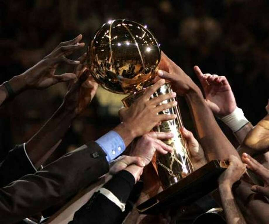 Members of the San Antonio Spurs reach for the NBA Championship trophy after defeating the Detroit Piston,81 - 74, in game seven of the NBA finals in San Antonio, Thursday, June 23, 2005. (AP Photo/Joe Cavaretta) (AP)