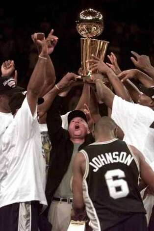 San Antonio Spurs' owner Peter Holt, center, holds the NBA Championship trophy with his team after the Spurs defeated the New York Knicks 78-77 in Game 5 of the 1999 NBA Finals on Friday, June 25, 1999, at New York's Madison Square Garden. (AP Photo/Kathy Willens) (AP)