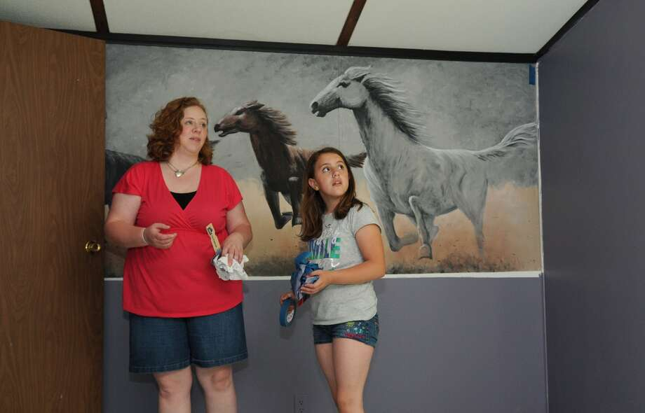 Dana Riecken, from left, and her daughter, Samantha, a fourth-grader at Huffman Intermediate, check out one of the bedrooms in their new home. Freelance photo by Jerry Baker Photo: Jerry Baker