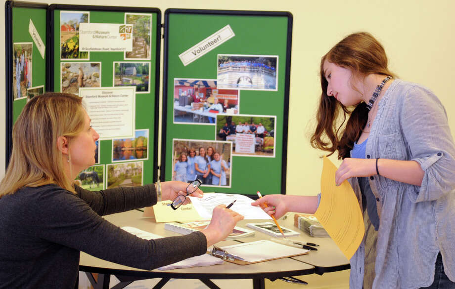 Jenni Barker gets information from Cathryn Oulighan, Head of volunteers and interns at Stamford Museum and Nature Center during Tuesday's volunteer fair at The Academy of Information Technology and Engineering on May 22, 2012. Photo: Lindsay Niegelberg / Stamford Advocate