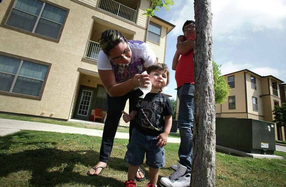 Genia Machado cleans son Alius Machado's face as husband Elijah Machado stands nearby outside the Mission Del Rio apartments on the South Side. Photo: BOB OWEN, San Antonio Express-News / © 2012 San Antonio Express-News