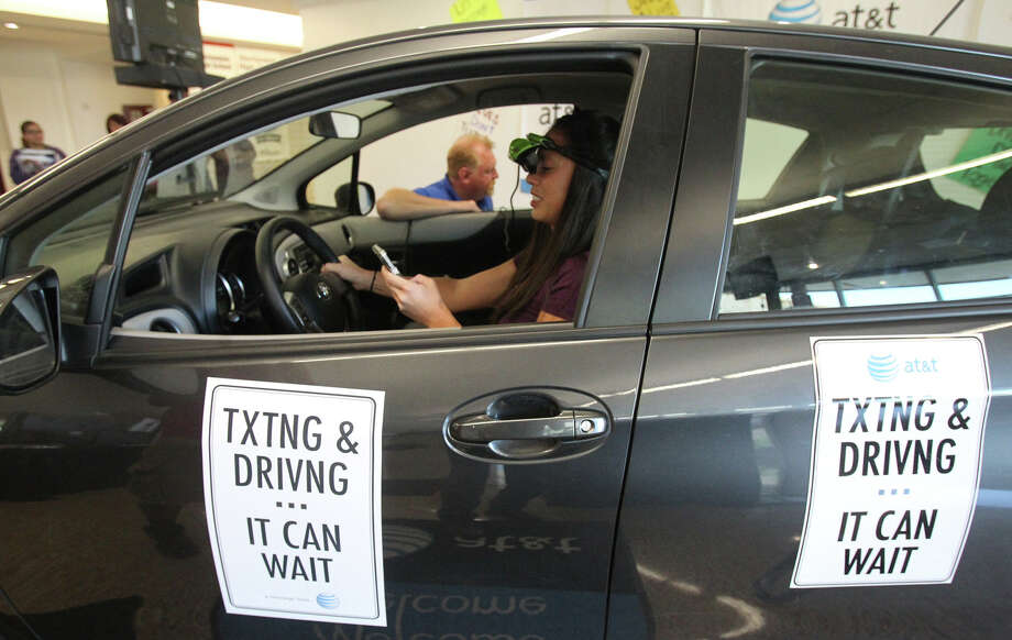 Harlandale High School math teacher Angie Milani sits behind the wheel of a Toyota and tries to text on her cell phone while operating a driving simulator at Harlandale High School Tuesday May 22, 2012. Milani and students at the school were participating in the AT&T Texting & Driving...It Can Wait Campaign. The program's goal is to illustrate the dangers of driving while texting. Photo: John Davenport, San Antonio Express-News / SAN ANTONIO EXPRESS-NEWS (Photo can be sold to the public)