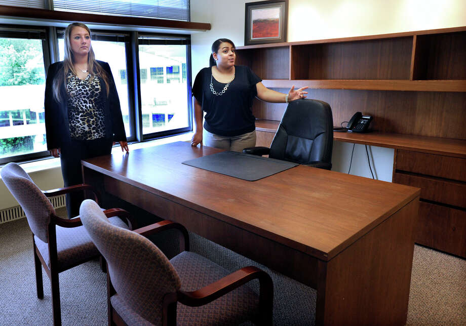 Brianna Nelson, left, executive project co-ordinator for Matrix, and Yoselin Reinoso, general manager for Matrix Executive Suites, shows ones of the offices available for rent, Tuesday, May 22, 2012. Photo: Carol Kaliff / The News-Times