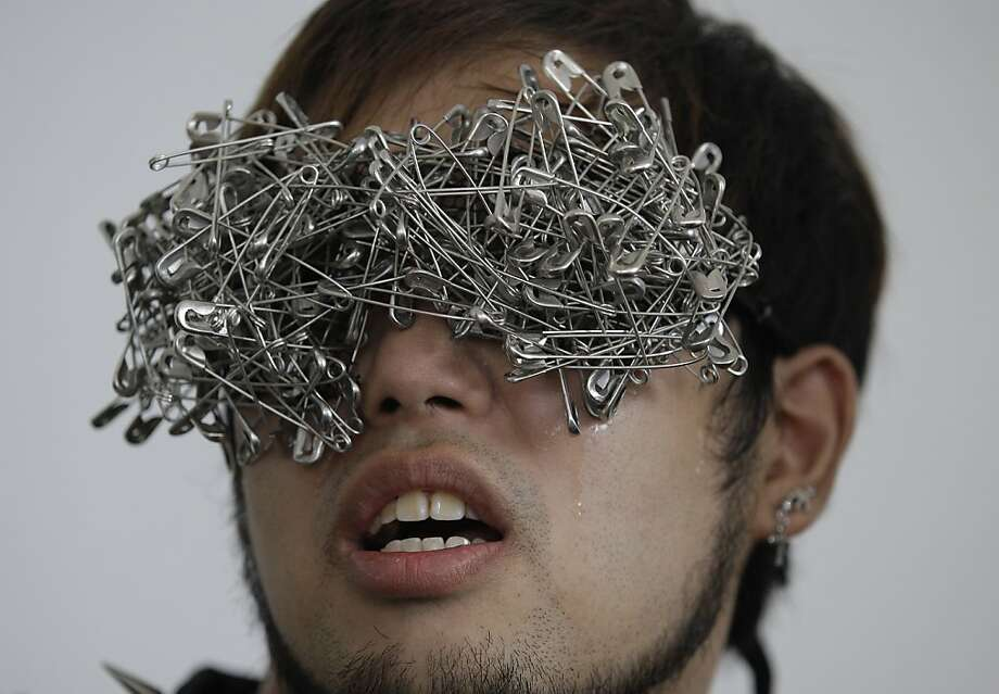 "A Filipino fan of pop star Lady Gaga wears eyewear made of pins as he waits outside the concert venue before her performance in suburban Pasay, south of Manila, Philippines on Monday May 21, 2012. Authorities in the conservative, majority Roman Catholic country approved the concerts, set for tonight, May 21, and Tuesday, but said they won't allow nudity or lewd acts. A religious group warned they will sue Lady Gaga and concert organizers if she sings ""Judas"" during her concert. (AP Photo/Aaron Favila) Photo: Aaron Favila, Associated Press"