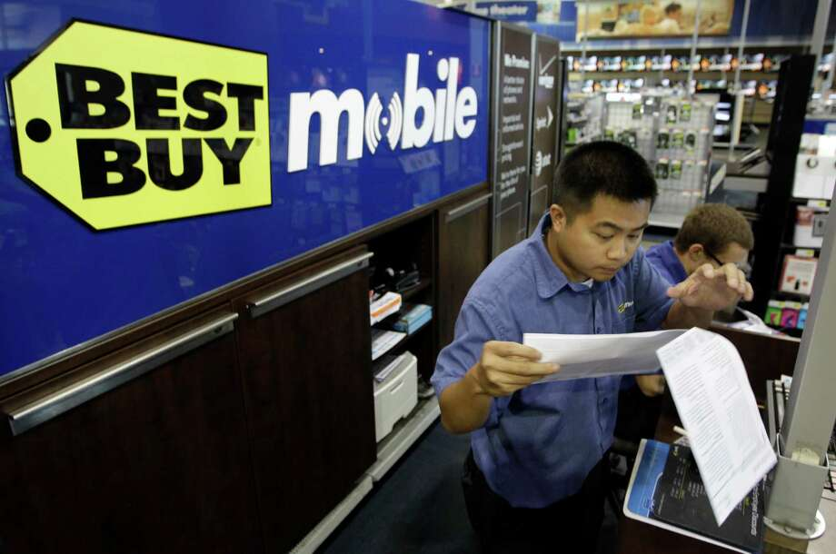 A Best Buy employee looks over a cellphone contract for a customer in Mountain View, Calif. Increasing competition from Internet retailers and discount stores is putting increasing pressure on the big-box chain. Photo: Paul Sakuma / AP2011