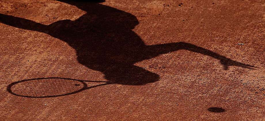 Japan's Tatsuma Ito casts a distinct shadow as he serves during a loss to Argentina's Leonardo Mayer during the Team World Cup. Photo: Frank Augstein / AP