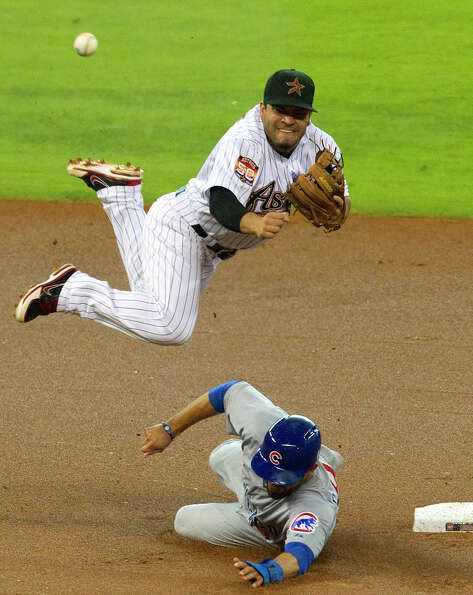 Houston Astros second baseman Jose Altuve is tripped up by Chicago Cubs David DeJesus as he makes a