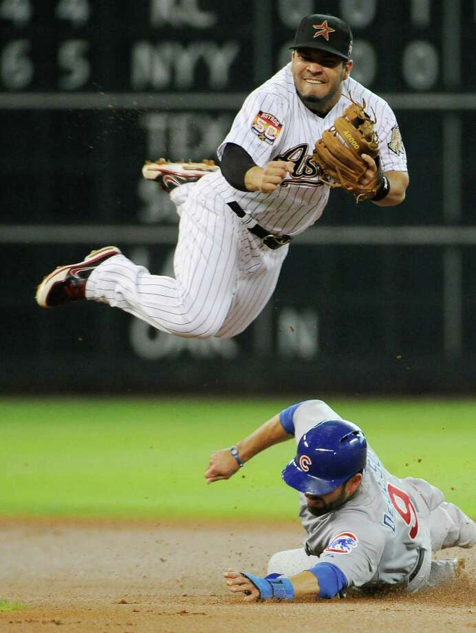 Houston's Jose Altuve takes the high to avoid the Cubs' David DeJesus, who is out at second. Photo: AP