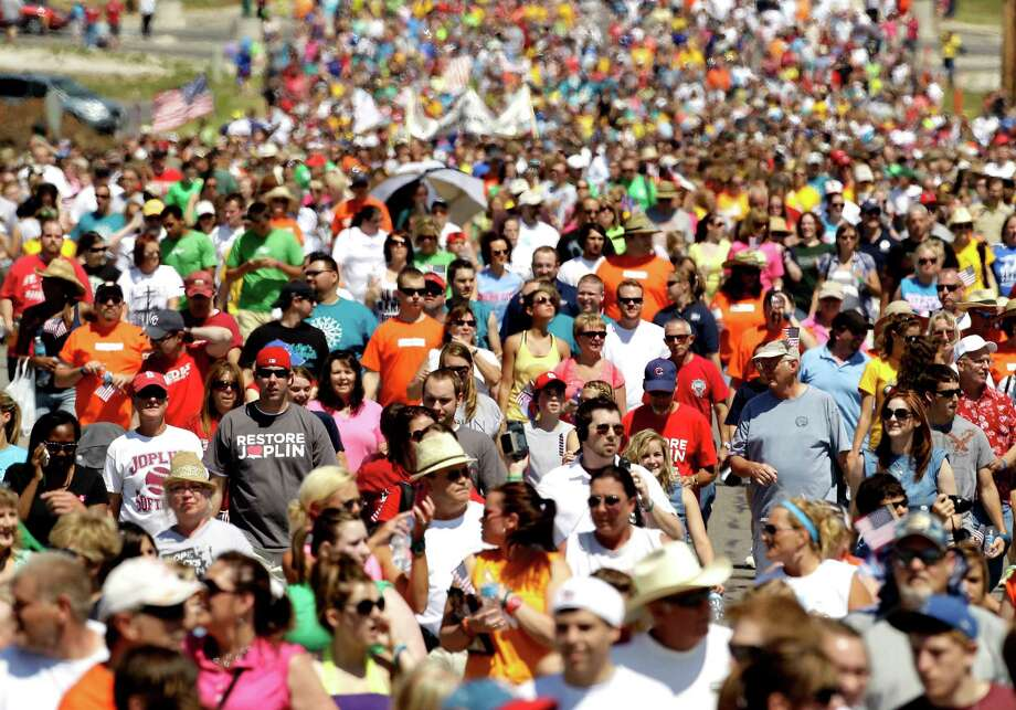 Thousands of people walk the path of destruction, Tuesday, May 22, 2012, in Joplin, Mo. The community is marking the anniversary of an EF-5 tornado that killed 161 people as it cut a wide swath through Joplin a year ago. (AP Photo/Charlie Riedel) Photo: Charlie Riedel