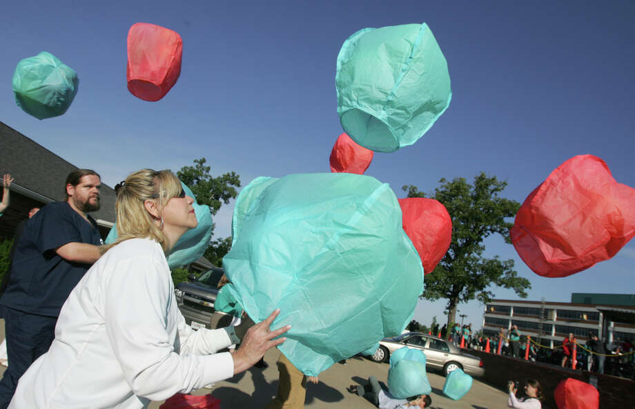 Renee Denton, director for medical oncology and pediatrics at Freeman Hospital, releases a lantern Tuesday, May 22, 2012 during Morning Has Broken event at Freeman Hospital.  The laterns were in remembrance of the May 22, 2011 tornado victims. The tornado killed 161 people and destroyed one-third of the city, making it the nation's deadliest single tornado in six decades.   (AP Photo/The Joplin Globe, Roger Nomer) Photo: Roger Nomer