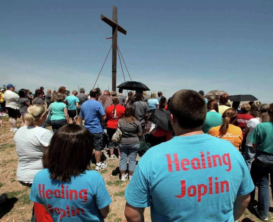 Parishioners gather around the cross at St. Mary's Catholic Church on Tuesday, May 22, 2012, in Joplin, Mo. The cross is all that remains of the church which was destroyed by a deadly tornado one year ago. The community is marking the anniversary of the twister that killed 161 people as it cut a wide swath through Joplin last year. (AP Photo/Charlie Riedel) Photo: Charlie Riedel