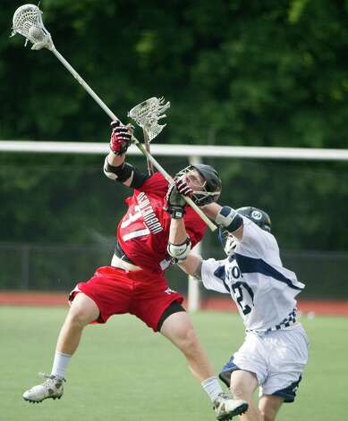 New Canaan's Eric Persky and Wilton's Sean Carroll battle for the ball as New Canaan and Wilton face off in the FCIAC boys lacrosse semifinals at Brien McMahon High School in Norwalk, Conn., May 22, 2012. New Canaan won the game, 11-6. Photo: Keelin Daly / Stamford Advocate