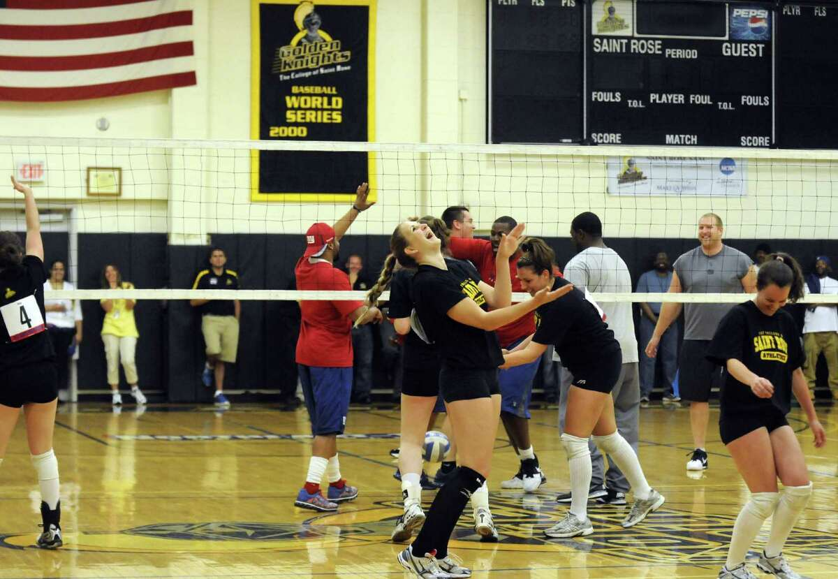 Members of the Saint Rose College women's volleyball team celebrate after defeating New York Giants veterans and rookies in an exhibition vollyeball game at the college in Albany N.Y. Tuesday May 22, 2012. (Michael P. Farrell/Times Union)