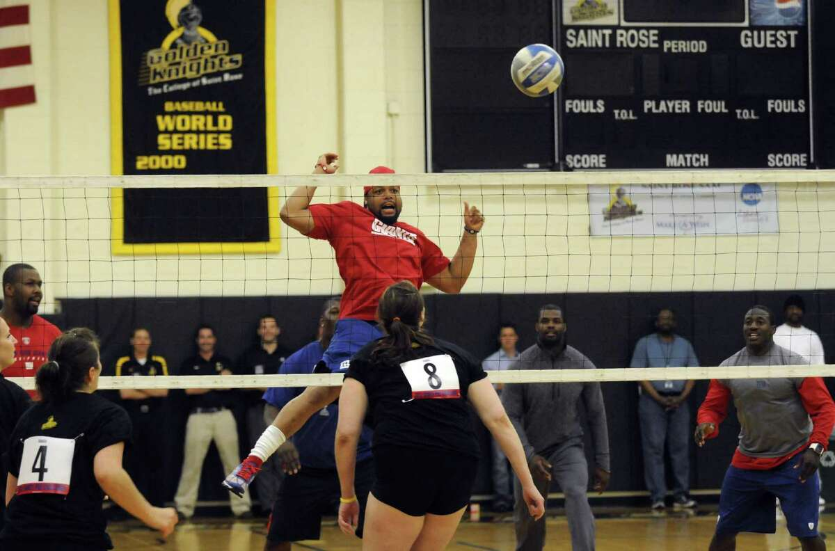New York Giants Da'Rel Scott, center, watches his return hit while playing the College of Saint Rose women's volleyball team in an exhibition volleyball game at the college in Albany N.Y. Tuesday May 22, 2012. (Michael P. Farrell/Times Union)