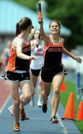 Ridgefield's Laura Hergenrother hands the baton to Madison Tannenbaum in the 4x800 meter relay during the FCIAC boys and girls track championships held Tuesday, May 22, 2012 at Danbury High School. Photo: Autumn Driscoll / Connecticut Post