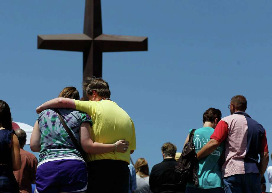 From left, Mary Black is comforted by her brother Scottie as Dawna Middleton and Bill Cook hug during a service at a cross, all that remains of St. Mary's church after a deadly tornado a year ago in Joplin, Mo. Photo: Joe Raedle / 2012 Getty Images