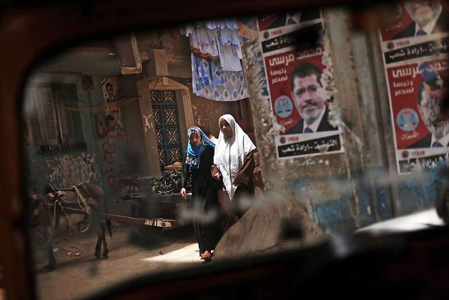 Two Egyptian women walk past posters of Muslim Brotherhood presidential candidate Mohammed Morsi, in Matariya slum in Cairo, Egypt, Tuesday, May 22, 2012. The May 23-24 presidential election is the first since last year's ouster of longtime authoritarian ruler Hosni Mubarak, marking the first time Egyptians will choose their leader in a race overseen by international monitors. (AP Photo/Manu Brabo) Photo: Manu Brabo, Associated Press