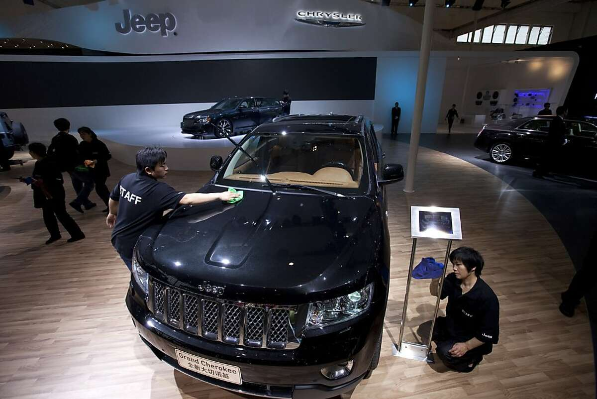 Cleaners prepare a Jeep Grand Cherokee at the Beijing International Automotive Exhibition in Beijing, China, Tuesday, April 24, 2012. (AP Photo/Alexander F. Yuan)
