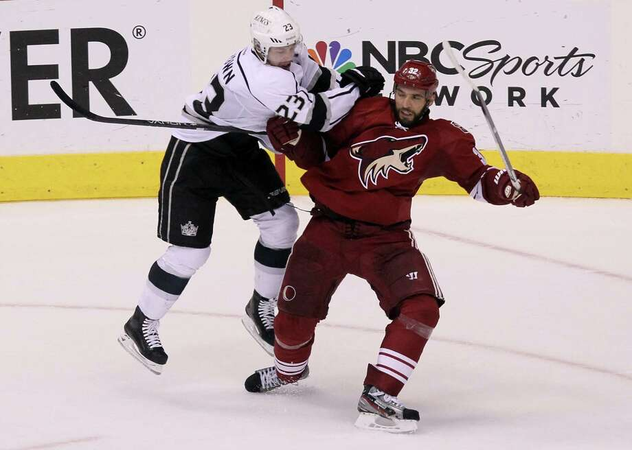 The Kings' Dustin Brown, left, leaves the ice to take a run at the Coyotes' Michal Rozsiva during Game 5, which required overtime to decide. Photo: Jeff Gross / 2012 Getty Images