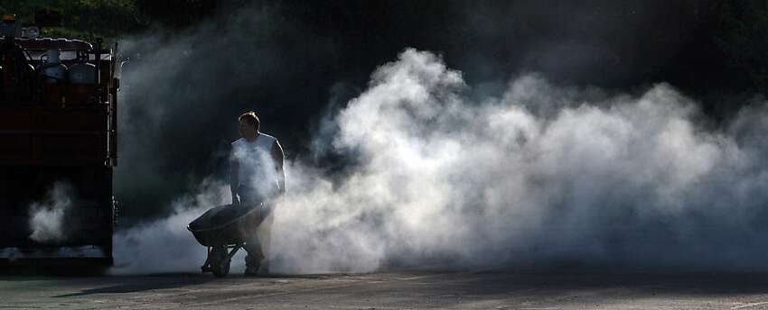 Blacktopper Jake Wanta pushes a wheelbarrow full of blacktop mix through a cloud of steam as he works to repair a parking lot at a hospital in Wausau, Wis., Tuesday, May 22, 2012. (AP Photo/Wausau Daily Herald, Dan Young)