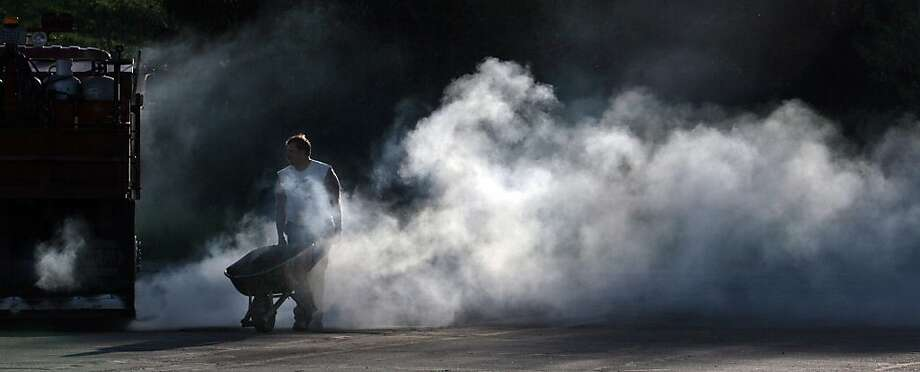 Blacktopper Jake Wanta pushes a wheelbarrow full of blacktop mix through a cloud of steam as he works to repair a parking lot at a hospital in Wausau, Wis., Tuesday, May 22, 2012. (AP Photo/Wausau Daily Herald, Dan Young) Photo: Dan Young, Associated Press