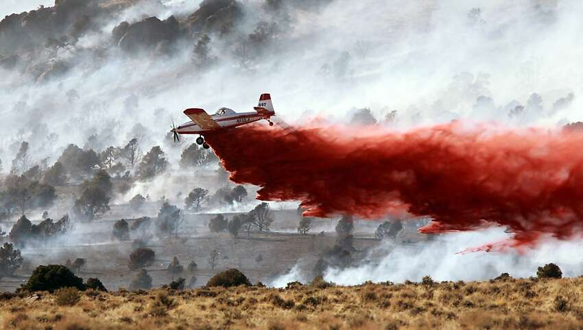 Firefighters battle a wildfire south of Gardnerville, Nev., on Tuesday, May 22, 2012. The fast-moving blaze near the Nevada-California line destroyed at least two homes on Tuesday as it forced evacuations and sent up huge plumes of black smoke, witnesses said. (AP Photo/Cathleen Allison)
