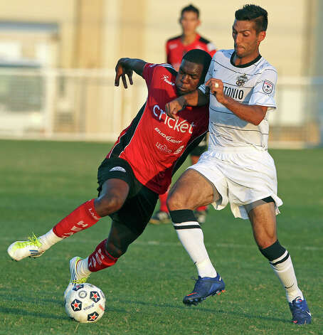 Laredo's Greg Mulamba leans into Jonathan Greenfield as he advances the ball as the San Antonio Scorpions play the Laredo Heat in a U.S. Open Cup game at Blossom Soccer Stadium on May 22, 2012. Photo: Tom Reel, Express-News / ©2012 San Antono Express-News