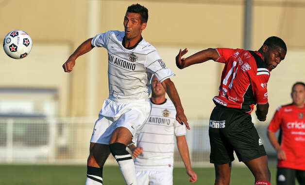 San Antonio's Jonathan Greenfield moves the ball away from Greg Mulamba as the San Antonio Scorpions play the Laredo Heat in a U.S. Open Cup game at Blossom Soccer Stadium on May 22, 2012. Photo: Tom Reel, Express-News / ©2012 San Antono Express-News