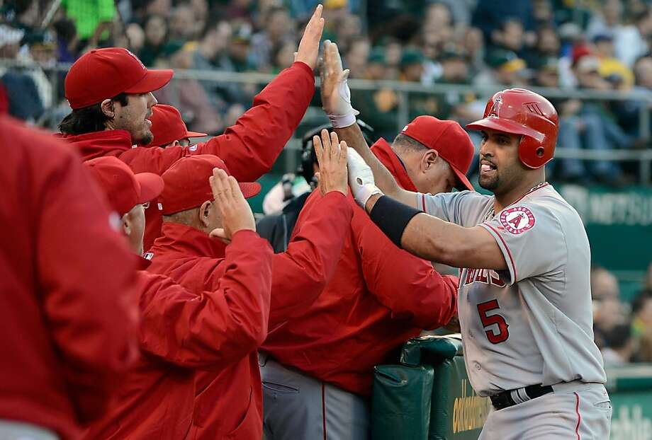 OAKLAND, CA - MAY 22:  Albert Pujols #5 of the Los Angeles Angels of Anaheim slaps hands with teammates back in the dugout after hitting a solo home run in the third inning against the Oakland Athletics at O.co Coliseum on May 22, 2012 in Oakland, California.  (Photo by Thearon W. Henderson/Getty Images) Photo: Thearon W. Henderson, Getty Images