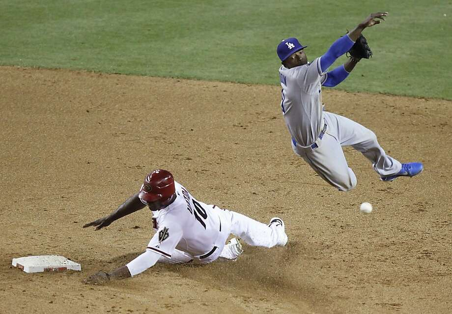 Los Angeles Dodgers shortstop Dee Gordon, right, leaps to avoid the slide by Arizona Diamondbacks' Justin Upton, left, to complete a double play for the final outs of the game in the ninth inning of a baseball game Tuesday, May 22, 2012, in Phoenix. The Dodgers won 8-7.(AP Photo/Paul Connors) Photo: Paul Connors, Associated Press