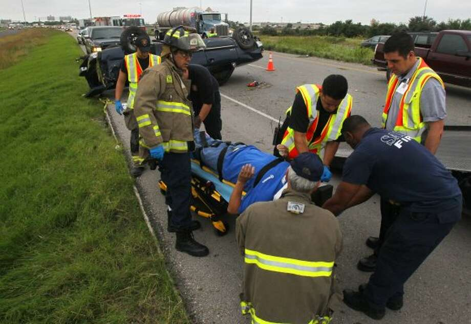 """San Antonio firefighters and paramedics prepare to transport the driver of a Chevy pickup truck that rolled over after colliding with a Ford Explorer around 6:30 a.m. Wednesday on Loop 410 near the Space Center exit. John Pearson, the driver of the Explorer, said the driver of the truck changed lanes several times and the two vehicles """"bumped"""" and the truck flipped. The truck's driver was transported to an area hospital with non-life threatening injuries. Traffic was backed up on Loop 410 for about an hour and a half. (San Antonio Express-News)"""