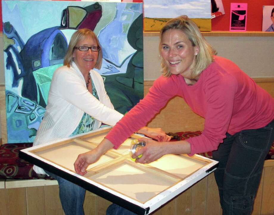 Christine Bang and Meg Tweedy, co-chairmen of the 54th annual Darien Art Show, prepare a painting for admission. Art will be received at the Darien Arts Center in Darien, Conn., Sunday, May 27, from noon to 4 p.m. and Tuesday, May 29 from 4 to 8 p.m. Photo: Contributed Photo