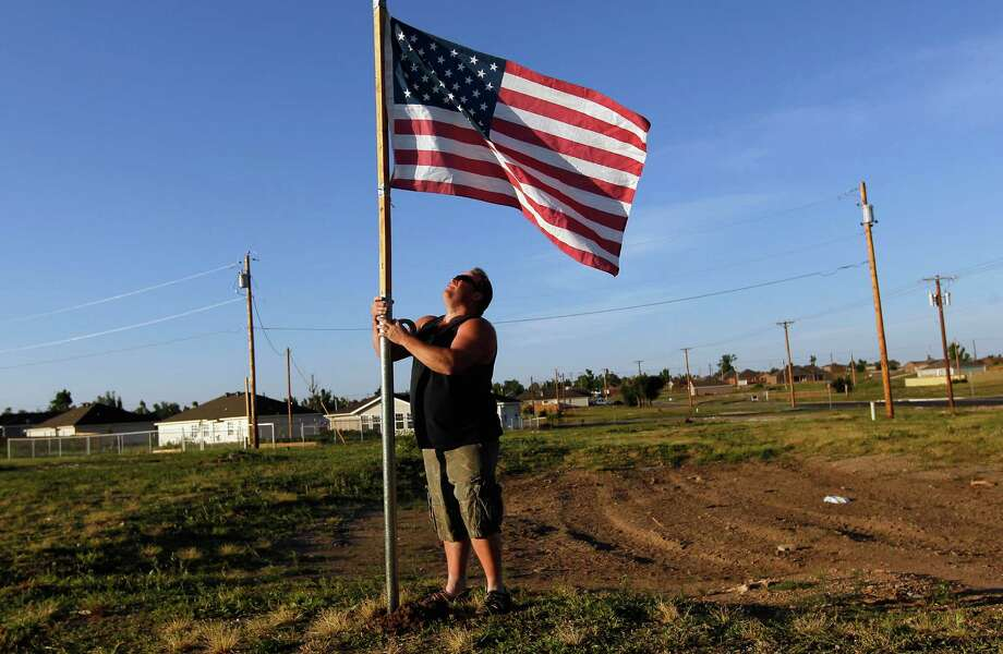 JOPLIN, MO - MAY 22:  Scott Hasty places an American flag next to where his house was before it was destroyed by the massive tornado that passed through the town one year ago today on May 22, 2012 in Joplin, Missouri.  Scott said he was in the house when the EF-5 tornado hit leaving behind a path of destruction along with 161 deaths and hundreds of injuries, but one year later there are signs that the town is beginning to recover.  (Photo by Joe Raedle/Getty Images)  *** BESTPIX *** Photo: Joe Raedle, Getty Images / 2012 Getty Images