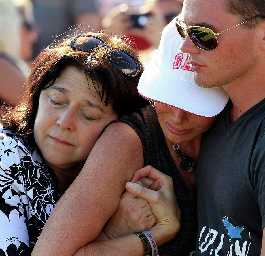 Family friend Carole Liston, left, hugs Marilyn Sixx and her son Chris Sixx during a ceremony marking the anniversary of a deadly tornado that devastated Joplin, Mo. a year ago on Tuesday, May 22, 2012. The twister killed 161 people as it cut a wide swath through Joplin. Photo: Charlie Riedel, AP / AP