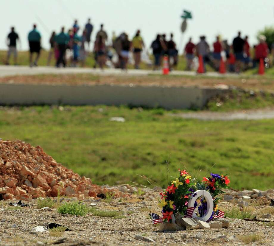 People walk past a memorial to tornado victims who died in a nursing home along path of destruction on the anniversary of a deadly tornado that devastated the area a year ago, Tuesday, May 22, 2012, in Joplin, Mo. The community is marking the anniversary the twister that killed 161 people as it cut a wide swath through Joplin last year. Photo: Charlie Riedel, AP / AP