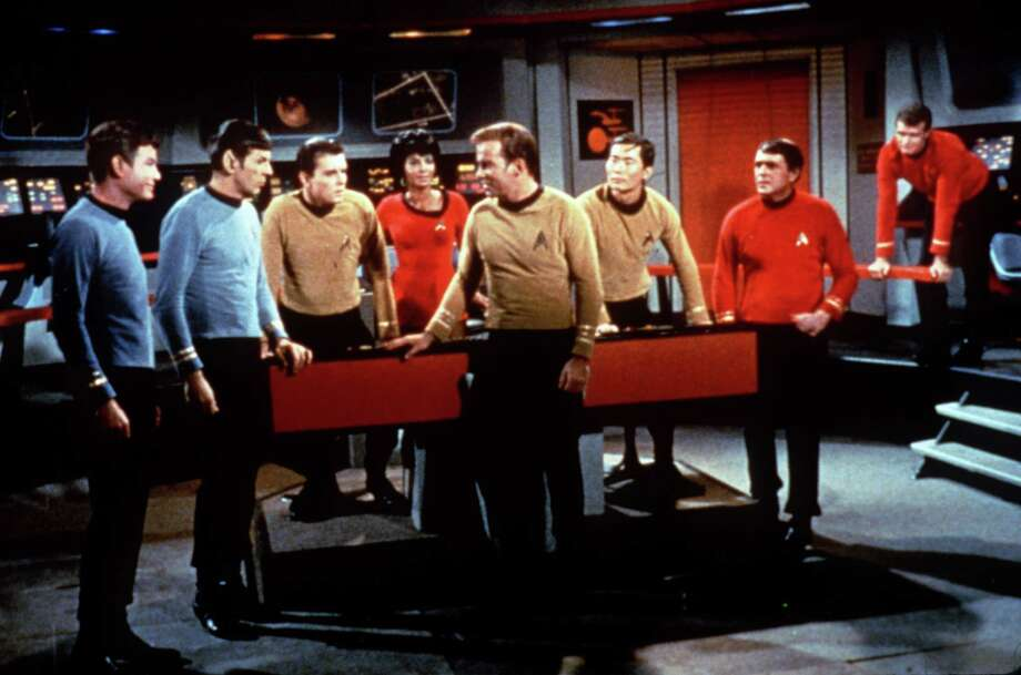 Star Trek --  The original series cast - William Shatner (center foreground), (l-r) DeForest Kelley, Leonard Nimoy, Walter Koenig, Nichelle Nichols, George Takei, James Doohan and an unidentified actor. / Handout slide