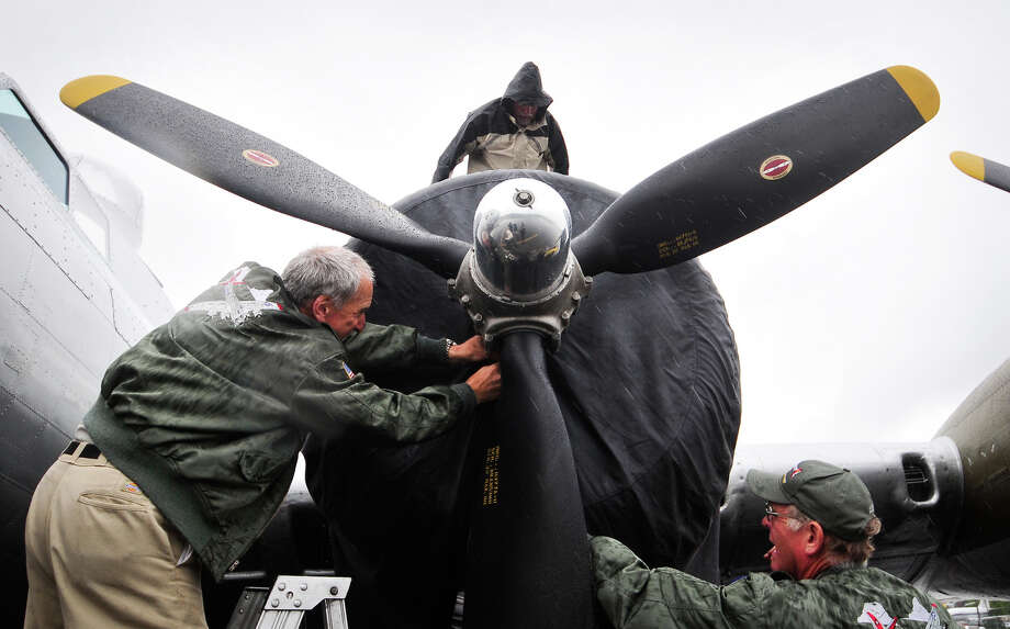 "Neil Morrison, left, and other crew members secure a tarp over an engine of ""Aluminum Overcast"" at the Museum of Flight in Seattle on Monday, May 21, 2012. The WWII-era B-17 ""Flying Fortress"" bomber is one of only a dozen remaining airworthy aircraft. From May 24 through 27, the Experimental Aircraft Association and the Museum of Flight will offer ground tours and ""mission"" flights over the Seattle area for a fee. Photo: LINDSEY WASSON / SEATTLEPI.COM"