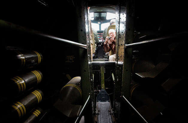 "Decorated B-17 pilot Emerson Tolle, 90, takes a photo of the bomb storage racks during a flight of ""Aluminum Overcast"" on Monday, May 22, 2012. The WWII-era B-17 ""Flying Fortress"" bomber is one of only a dozen remaining airworthy aircraft. From May 24th thru the 27th, EAA and the Museum of Flight will offer ground tours and ""mission"" flights for a fee. Photo: LINDSEY WASSON / SEATTLEPI.COM"