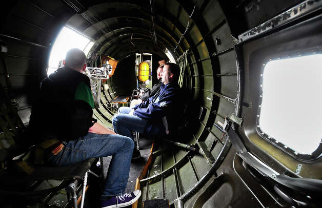 "Passengers look out of a gunner's window during a flight of ""Aluminum Overcast"" on Monday, May 21, 2012. The WWII-era B-17 ""Flying Fortress"" bomber is one of only a dozen remaining airworthy aircraft. From May 24th thru the 27th, EAA and the Museum of Flight will offer ground tours and ""mission"" flights for a fee. Photo: LINDSEY WASSON / SEATTLEPI.COM"