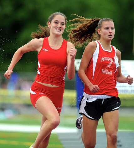 Greenwich's Abigail Markowitz, left, and Fairfield Warde's Cate Allen race side by side during the last leg of the 1600 meter run at the FCIAC boys and girls track championships held Tuesday, May 22, 2012 at Danbury High School. Photo: Autumn Driscoll / Connecticut Post