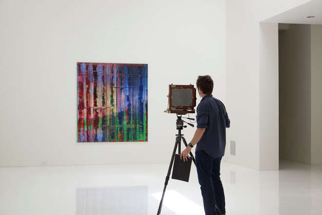 Photographer Adam Schreiber photographs a Gerhard Richter painting in Linda Pace's CAMPstreet penthouse apartment.