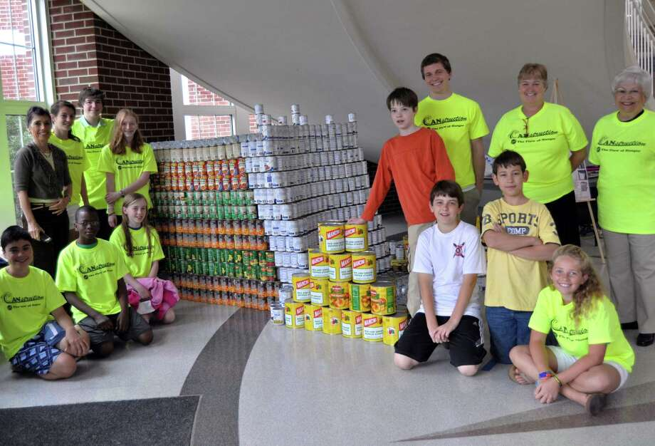Members of the Canstruction Club are pictured with their teacher advisor MaryEllen Flaherty-Ludwig (on left by window) and architect James Hall, principal Debi Boccanfuso and administrative assistant Etta Guarino at Middlesex Middle School in Darien, Conn. Photo: Contributed Photo