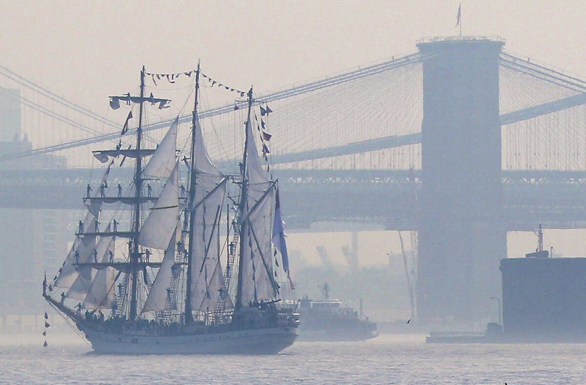 Tall ships travel up the Hudson River past New York City bridges as seen from Bayonne, N.J., Wednesday. Naval vessels ranging from a U.S. amphibious assault ship to a Finnish minelayer are participating in New York City's Fleet Week. (AP Photo/Seth Wenig)
