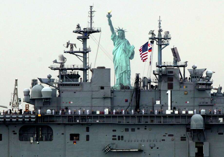 Sailors line the deck of the USS Wasp as she sails by the Statue Of Liberty, in New York,  to participate in Fleet Week activities Wednesday. (AP Photo/Richard Drew) Photo: Associated Press
