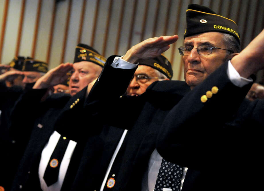 Veterans salute the flag during the Pledge of Allegiance at the Memorial Day program at Trinity Catholic High School on Wednesday, May 23, 2012. Photo: Lindsay Niegelberg / Stamford Advocate