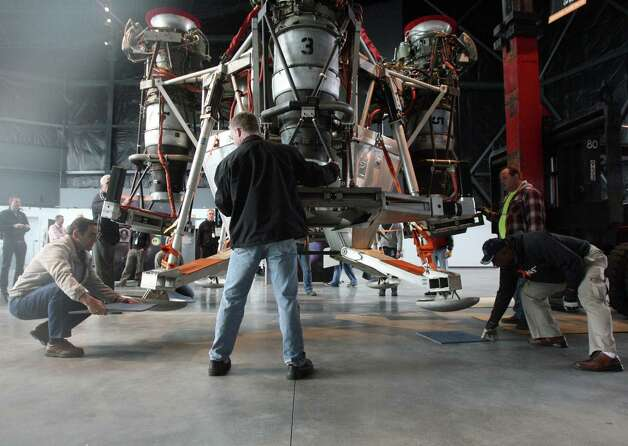 Workers position pads under Charon, a vehicle that commercial spaceflight company Blue Origin used to test vertical takeoff and landing, in the Seattle Museum of Flight's Space Gallery on Tuesday, May 23, 2012. Photo: Aubrey Cohen/seattlepi.com
