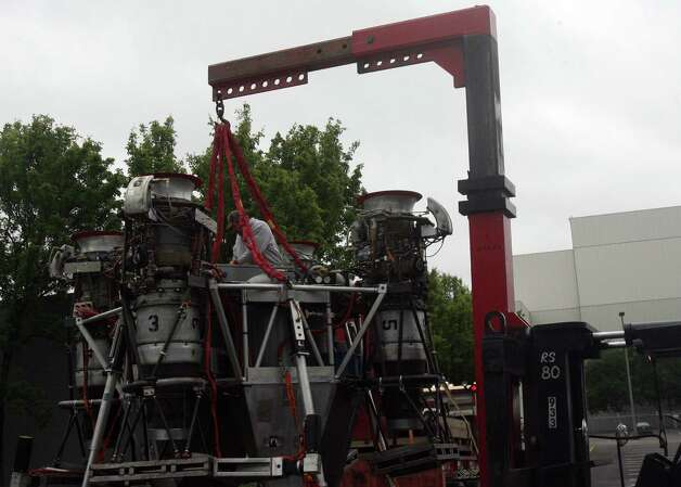 A worker attaches  cables to Charon, a vehicle that commercial spaceflight company Blue Origin used to test vertical takeoff and landing, so a crane can lift it off a flat-bed truck outside of the Seattle Museum of Flight's Space Gallery on Tuesday, May 23, 2012. Photo: Aubrey Cohen/seattlepi.com