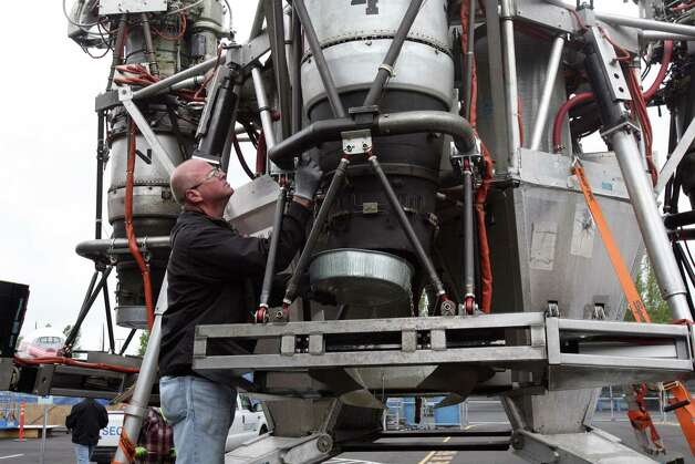 A worker attaches a pan to catch oil dripping from an engine of Charon, a vehicle that commercial spaceflight company Blue Origin used to test vertical takeoff and landing, as it arrives at Seattle's Museum of Flight on long-term loan on Tuesday, May 23, 2012. Photo: Aubrey Cohen/seattlepi.com