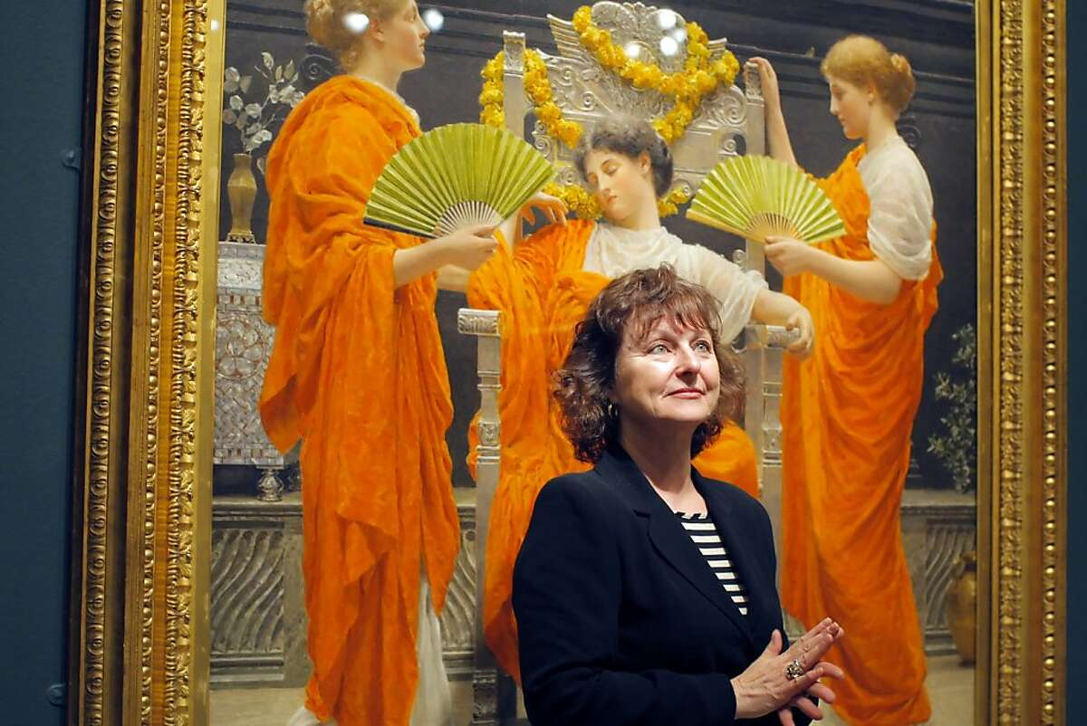 Curator Lynn Orr poses for a picture in front of Albert Moore's